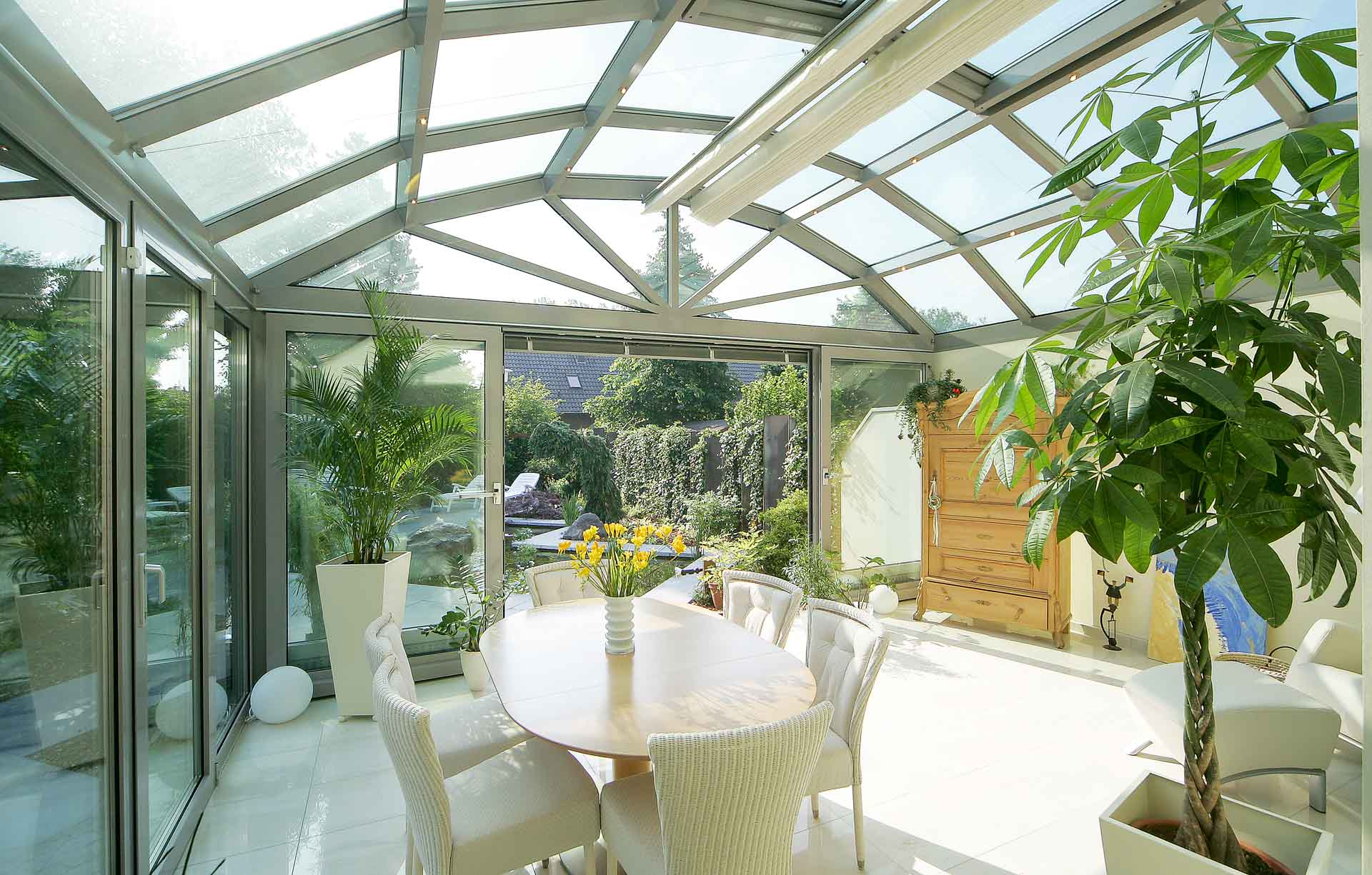 Terraced house conservatory with segmental arched roof in Oberhausen. Airy room height despite compliance with the construction heights at the neighbouring borders - ideal winter garden design for terraced house construction.